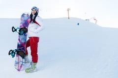 Morena com o snowboard em montanhas fotos de stock royalty free