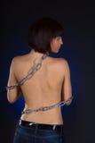 Morena com parte traseira do nude nas correntes sobre o fundo preto Fotos de Stock Royalty Free