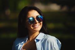 Morena com sorriso do brilho nos óculos de sol que olham o sol Imagem de Stock