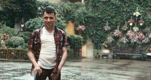 A morena considerável na roupa ocasional com bastão e sorriso bonito está olhando in camera durante a chuva no jardim de florescê video estoque
