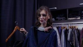 Morena consideravelmente nova que escolhe a roupa no vestuário em casa video estoque