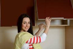 A morena da dona de casa no armário home da cozinha da roupa abre Foto de Stock Royalty Free