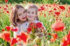 A morena da mãe no branco com filha junto em papoilas vermelhas de florescência coloca imagens de stock