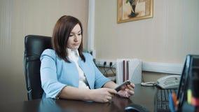 A morena da mulher de negócios em um casaco azul sentou-se para baixo em sua cadeira no escritório e começou-se trabalhar no tecl vídeos de arquivo