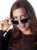 Morena de sorriso bonita que olha sobre seus óculos de sol Imagens de Stock Royalty Free