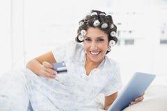 Morena de sorriso nos encrespadores de cabelo que encontram-se em sua cama usando sua tabuleta para comprar em linha Fotos de Stock