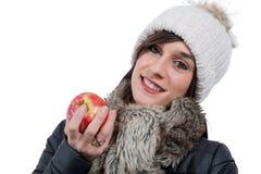 Morena de sorriso nova com o tampão do inverno, comendo uma maçã Fotografia de Stock Royalty Free