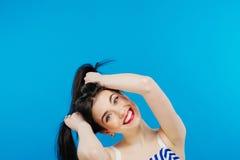 Morena de sorriso que faz dois rabos de cavalo pelas mãos que têm o divertimento no estúdio no fundo azul fotografia de stock