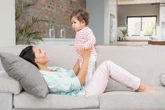 Morena de sorriso que joga com seu bebê foto de stock royalty free