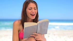 Morena de sorriso que lê uma novela interessante vídeos de arquivo