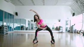 Morena desportiva que faz os exercícios em sapatas do kangoo vídeos de arquivo