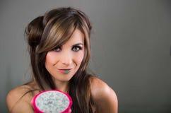 A morena do Headshot, o olhar escuro da mística e o batom verde, sustentando dois halfs abertos do pitaya cor-de-rosa frutificam  Fotografia de Stock