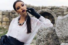 A morena elegante veste a camisa, a saia do couro e as luvas brancas Fotos de Stock
