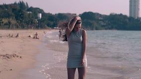 Morena em corridas curtos do vestido e das voltas no movimento lento da praia sobre filme