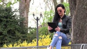 Morena em um banco da rua com uma tabuleta vídeos de arquivo