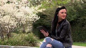 Morena em um banco da rua com uma tabuleta filme
