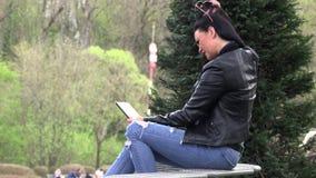 Morena em um banco da rua com uma tabuleta video estoque