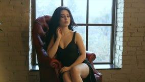 A morena em um vestido preto senta-se em uma poltrona de couro vídeos de arquivo