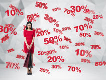 Morena em um vestido vermelho com os sacos de compras Símbolos do disconto e da venda: 10% 20% 30% 50% 70% Fundo contemporâneo Fotos de Stock Royalty Free