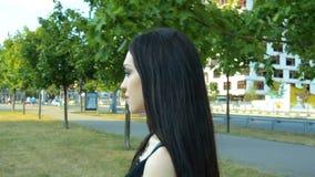 A morena encantador atravessa lentamente o parque em um dia ensolarado filme