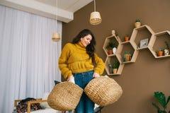 A morena encantador com as duas cestas que levantam no apartamento fotos de stock
