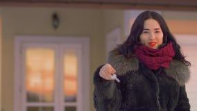 A morena encantador com bordos vermelhos agita chaves de sua casa nova filme