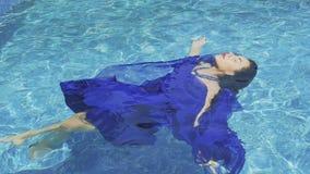A morena encantador com os bordos vermelhos no vestido azul nada na associação em slowmotion vídeos de arquivo