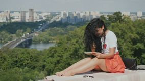 A morena encantador relaxa com a tabuleta no fundo da cidade filme
