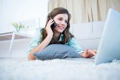 Morena feliz no telefone usando seu portátil fotos de stock