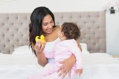 Morena feliz que mostra o pato amarelo a seu bebê Fotografia de Stock