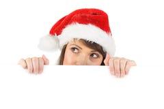 Morena festiva que guarda um cartaz ao olhar acima Fotos de Stock