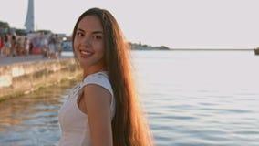 A morena impressionante com cabelo longo vestiu-se no vestido apertado branco que está pelo mar vídeos de arquivo