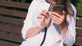 A morena irreconhecível da mulher datilografa uma mensagem no telefone celular que senta-se no banco no parque filme