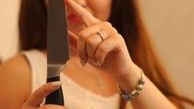 A morena irritada está verificando a agudeza da faca com o dedo video estoque