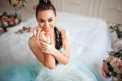 A morena lindo da noiva sorri e senta-se na cama Felicidade e alegria ao dia do casamento fotografia de stock royalty free