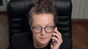 A morena madura da mulher nos vidros fala o telefone que senta-se na cadeira vídeos de arquivo