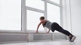 A morena magro bonita está fazendo algumas flexões de braço no gym filme