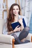 Morena magro nova atrativa com um livro azul Imagem de Stock Royalty Free