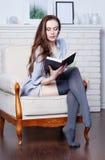 A morena magro nova atrativa está sentando-se em uma cadeira confortável grande Foto de Stock