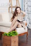 A morena magro nova atrativa está sentando-se em uma cadeira confortável grande Está lendo um livro Imagem de Stock