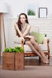 A morena magro nova atrativa está sentando-se em uma cadeira confortável grande pela chaminé Foto de Stock