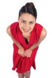 Morena misteriosa de sorriso no levantamento vermelho do vestido Imagens de Stock Royalty Free