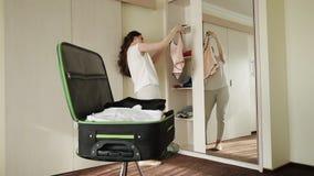 A morena no hotel recolhe coisas em uma mala de viagem filme