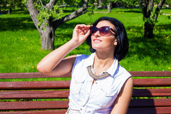 Morena nos óculos de sol que riem no parque em um dia ensolarado Fotos de Stock Royalty Free