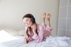 Morena nos pijamas cor-de-rosa que escutam a música com os fones de ouvido na cama Imagens de Stock Royalty Free