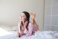 Morena nos pijamas cor-de-rosa que escutam a música com os fones de ouvido na cama Fotografia de Stock