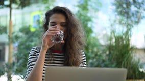 Morena nova atrativa do cabelo encaracolado que trabalha com portátil fora vídeos de arquivo