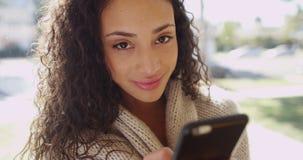 Morena nova atrativa em um telefone celular que sorri na câmera Fotografia de Stock Royalty Free