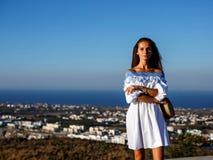 A morena nova bonita em um vestido branco está no backgrou fotos de stock royalty free