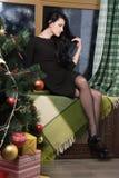 Morena nova bonita em um vestido preto que senta-se em uma soleira coberta com um cabo quadriculado fotografia de stock royalty free